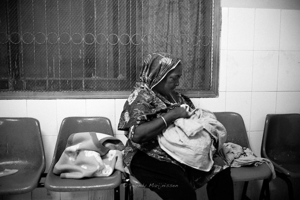 Chanda's mother looks at her newborn grandchild while doctors are still finishing the emergency surgery on Chanda. Karachi, Pakistan, 2010