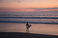 Pink Sunset over the Pacific Ocean and a surfer watching the waves. Santa Monica, CA 1.9.15