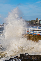 © Licensed to London News Pictures. 12/11/2018. Aberystwyth, UK. It's a stormy wild, but sunny morning in Aberystwyth, with strong winds gusting to over 30mph and high tides combining to drive huge waves into the sea defences around the promenade and harbour. Photo credit: Keith Morris/LNP