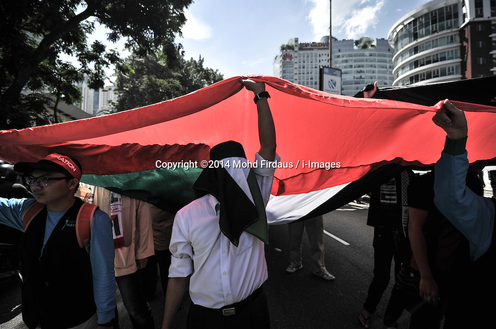 Image licensed to i-Images Picture Agency. 18/07/2014. Kuala Lumpur,Malaysia.Demonstrators hold a Palestine national flag as they protest against Israel's military action in Gaza during a demonstration in front of the US embassy in Kuala Lumpur on July 18, 2014.Picture by Mohd Firdaus / i-Images