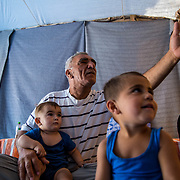 "Jameel sits with his grandson, Deyar, 1, on his lap, a neighbor to the right and his grandson and namsake, Jameel, in the foreground. They are Syrian Kurdish refugees from Aleppo. Jameel and his extended family have been in Ritsona for four months. With dwindling hope Jameel said, ""We will go anywhere as long as we can stay together."" Ritsona refugee camp, Greece, July 2016."