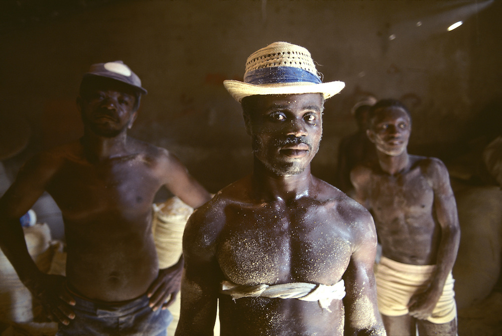 Haiti, Port-au-Prince, Men covered in dust while working in grain mill in La Saline in capital city