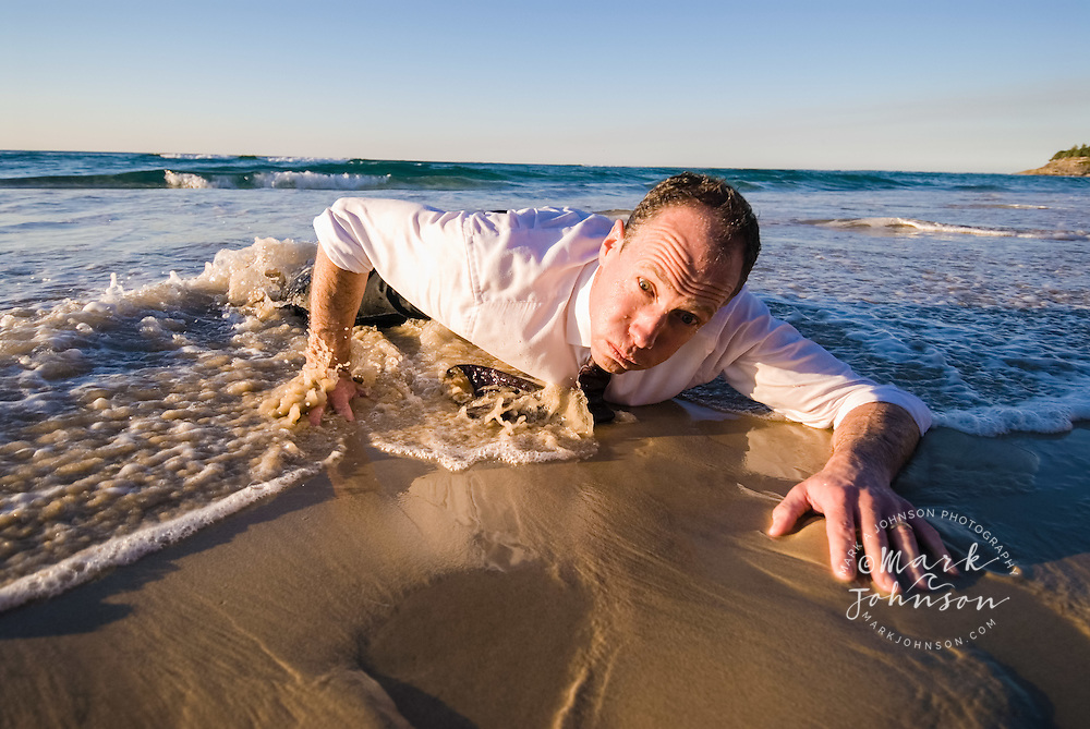 Businessman Crawling Up Beach