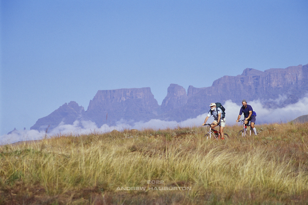 George Zaloumis & Carl Fatti mountain biking down Mike's Pass in the Cathedral Area, with the grand backdrop of peaks: Sterkhorn, Cathkin, Monk's Cowl and Champagne Castle, from left to right beyond. Ukhahlamba-Drakensberg Park, KwaZulu-Natal, South Africa.