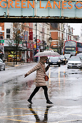 © Licensed to London News Pictures. 12/03/2019. London, UK. A woman crosses a flooded road on Green Lanes, Haringey in North London after a heavy downpour. Photo credit: Dinendra Haria/LNP