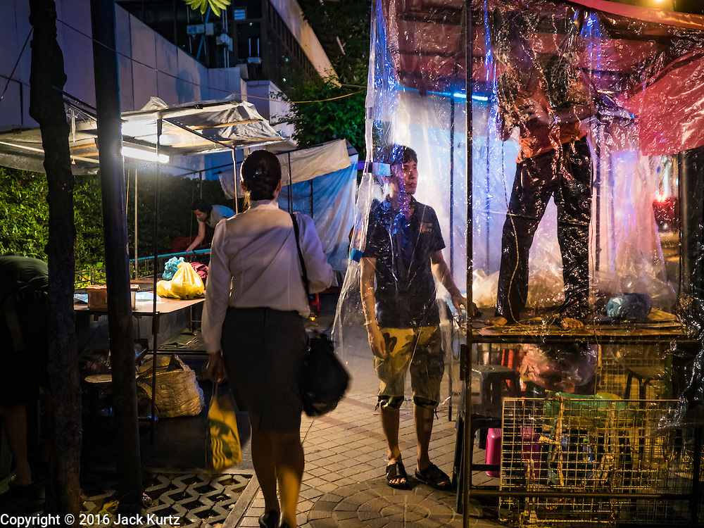 26 MAY 2016 - BANGKOK, THAILAND: Vendors at the Silom Road night market set up their booth. The night market on Silom Road, close to Bangkok's famous Patpong tourist area, is being closed by the Bangkok municipal government. Vendors have been told they have to leave the sidewalk on Silom Road by the end of May, 2016. The market is the latest street market being shut down by city officials as a part of the government's plan to clean up Bangkok. The Silom Road night market sells mostly tourist oriented clothes, inexpensive Thai art, and bootleg movies on DVD.       PHOTO BY JACK KURTZ