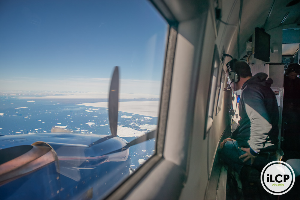 Dr. Thomas Krumpen, lead scientist of TIFAX campaign from Alfred Wegener Institute for Polar and Marine Research, monitors the ice on the way from Polar 6 research airplane from Greenland to Svalbard. Fram Strait, July 22, 2016, Esther Horvath / iLCP
