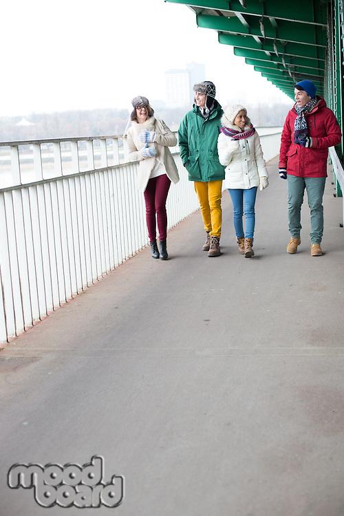Multiethnic friends walking on footpath during winter