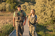 Father and daughter in waders walking together on footbridge while fly fishing Billingsley Creek Wildlife Managment area in Hagerman, Idaho. MR
