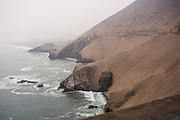 "Pan-American Highway 1 clings to a cliff above the South Pacific Ocean in the coastal desert north of Lima, in Peru, South America. From May to October along the coast of Peru, the heavy fog called ""garua"" blocks the sun but drops almost no rainfall, just a fine mist, enough to wet desert plants on high coastal hills. In contrast, around this time, the high Andes are generally sunny, warm, and dry (from June to September), great for trekking or touring."