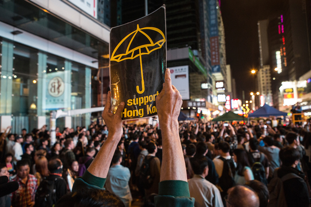 A protester holds up a sign calling on people to support Hong Kong in the quest for universal suffrage.
