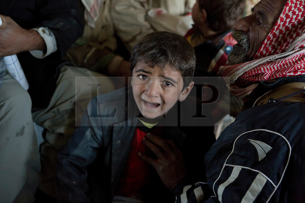 &copy; Licensed to London News Pictures. 11/12/2014. Sinjar Mountains, Iraq. A young Yazidi refugee cries after running a gauntlet of older and stronger refugees who pushed their way onto an Iraqi Air Force Mi-17 Hip helicopter that will evacuate he and his family.<br /> <br /> Although a well publicised exodus of Yazidi refugees took place from Mount Sinjar in August 2014 many still remain on top of the 75 km long ridge-line, with estimates varying from 2000-8000 people, after a corridor kept open by Syrian-Kurdish YPG fighters collapsed during an Islamic State offensive. The mountain is now surrounded on all sides with winter closing in, the only chance of escape or supply being by Iraqi Air Force helicopters. Photo credit: Matt Cetti-Roberts/LNP