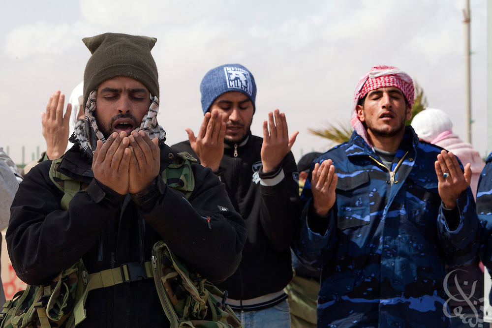 Libyan rebel fighters pray at their checkpoint position March 08, 2011 in Ras Lanouf, Libya. For more than 2 weeks rebels in Eastern Libya have been battling pro-Qadaffi forces, seeking to topple the nearly 42 year old dictatorship of Col Moammar el-Qadaffi.