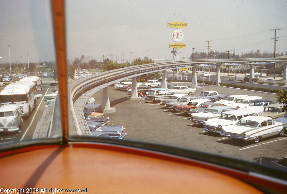 1960s cars seen from tram passing Disneyland hotel and Golf sign in parking lot. Disneyland vacation Kodachromes from 1962.