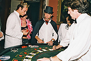 Costumed punters one wearing a crown another a top hat and cape, placing bets with a croupier at a card table, at Posh, Addington Palace, UK, August, 2004