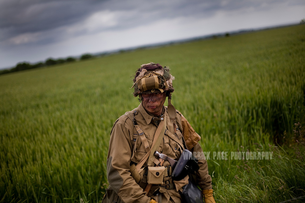 A WWII re-enactor stands in a field during the unveiling of a memorial June 6, 2012, in Sainte Marie-du-Mont, France. Normandy is the only place in the world that has seen a consistent mass-pilgrimage of war veterans returning to the lands where they fought. No other lands that have born witness to war - including other WWII battlefields - have drawn veterans back in the way that Normandy has. Along with the veterans come thousands of WWII historical enthusiast and family members of passed veterans. Sixty-eight years on the numbers of veterans returning to the beaches and fields where they fought dwindle, as age and time prevail. (Photo by Warrick Page)