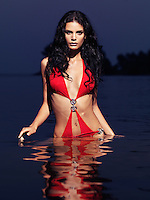 Beautiful young woman with long dark hair wearing a red swim suit walking out of water at night