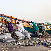 Des pêcheurs aident l'arrivée d'une des pirogues en fin de journée, à la plage de Soumbédioune, Dakar