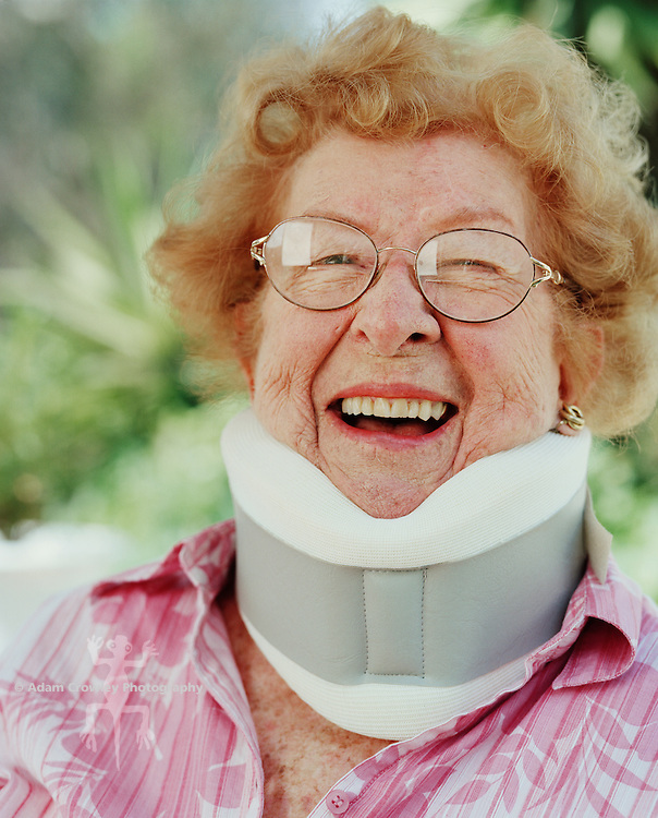Senior woman wearing neck brace, smiling, portrait