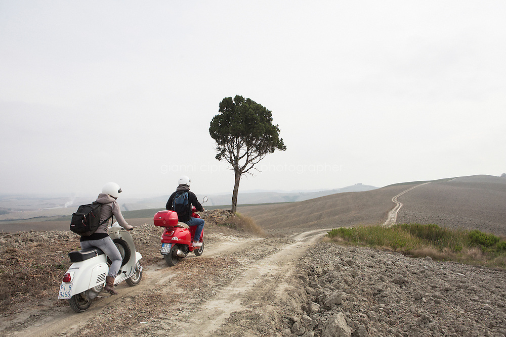 Asciano, Italy - 10 September 2014: Journalist Tina Nachtmann rides a Vespa 125 Primavera of 1974 on a road trip through Tuscany with her travel companion Michele, through the Crete Senesi in Asciano, Italy, on September 10th 2014.<br /> <br /> The Crete Senesi refers to an area of the Italian region of Tuscany to the south of Siena. It consists of a range of hills and woods among villages and includes the comuni of Asciano, Buonconvento, Monteroni d'Arbia, Rapolano Terme and San Giovanni d'Asso, all within the province of Siena. Crete senesi are literally &lsquo;Senese clays&rsquo;, and the distinctive grey colouration of the soil gives the landscape an appearance often described as lunar.