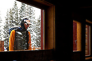 John Heisel reads the plaque in front of the Peter Estin hut while it snows outside.  Hut tours are very popular in Colorado where you enjoy warmth, safety and plenty of ammenities while in the backcountry.