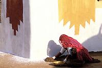 Inde - Rajasthan - Village peint des environs de Jaisalmer - Femme enduisant le sol de la cour