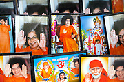 PUTTARPATHI, INDIA - 01st November 2019 - Close-up of printed photo postcards of Hindu Gods and the late Sathya Sai Baba for sale at a market stall in Puttarpathi, Andhra Pradesh, South India