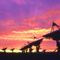 Silhouetted satellite dishes against dramatic sunset sky, near Socorro, New Mexico