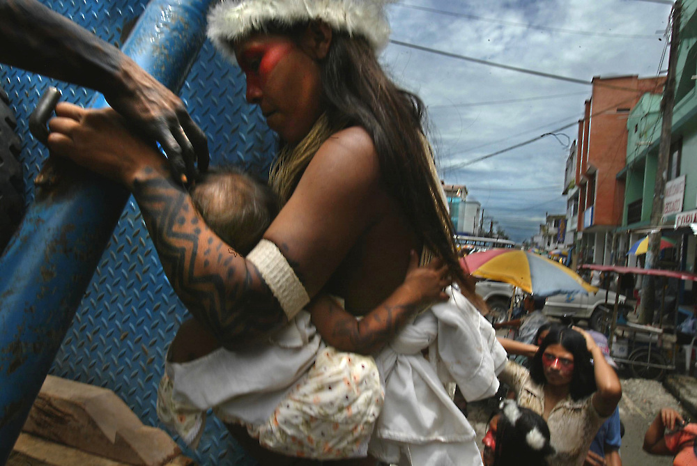 A Huaorani Indian woman gets helped up onto a truck bed where she and others from her tribe chanted protests from the makeshift stage in front of the courthouse  in Lago Agrio, Ecuador. The Indians chanted and danced with their children.