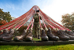 EDITORIAL USE ONLY<br /> Sapper Jamie Hutchinson from the Corps of Royal Engineers putting the finishing touches to 'Boots on the Ground' on display at Westferry Circus in LondonÕs Canary Wharf, as part of the UKÕs first Remembrance Art Trail in association with The Royal British Legion, which opens free to the public on Tuesday November 1 for two weeks.