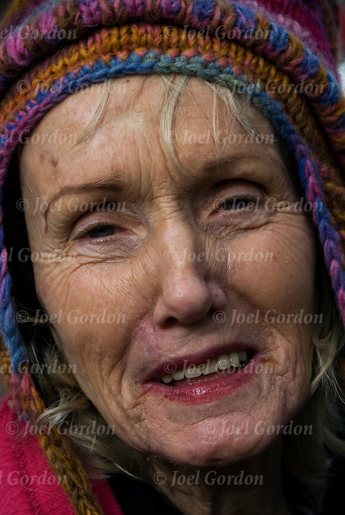 Elderly wrinkled face of woman in the crowd, head and shoulder smiling portrait, eye contacts looking into the camera