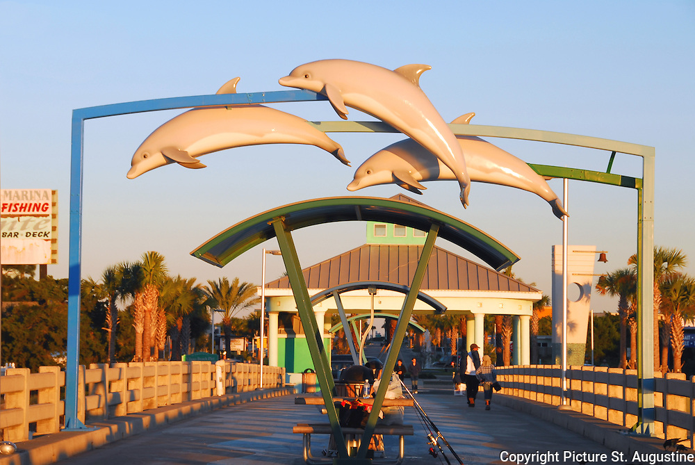 Dophins fly high over the pier in Vilano Beach Florida. This photograph was taken in the golden light of a late fall sunset. Vilano Beach is located in St. Augustine, Florida. St. Augustine is the oldest continually occupied city of European origin in the United States. The city was founded by Don Pedro Menendez de Aviles in 1565.