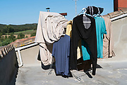 drying rack loaded with clothing and bed sheet