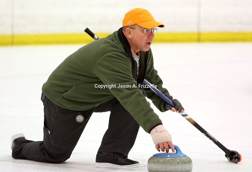Shep Sheppard delivers a stone during a curling match at the Wilmington Ice House. (Jason A. Frizzelle)