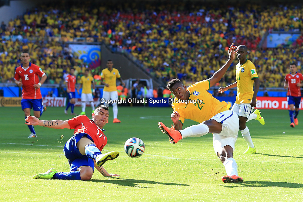28th June 2014 - FIFA World Cup - Round of 16 - Brazil v Chile - Jo of Brazil shoots as Gary Medel of Chile blocks - Photo: Simon Stacpoole / Offside.