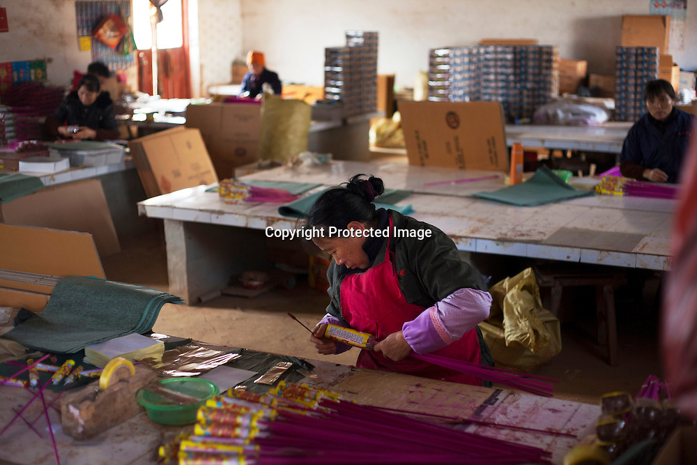 Hunan, Liuyang, Dec. 19..2013 : Xiao Chenying, a worker assembles  fireckrackers for the Western market in a factory .
