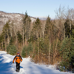 A man snowshoes on a woods road in Groton, New Hampshire.  Near Groton Hollow Road.