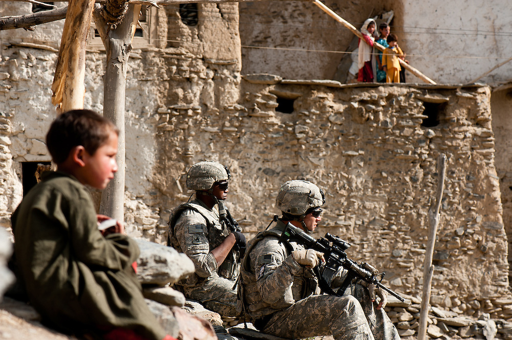 Children look on as American and Afghan soldiers search an Aghan family compound in the Jalrez Valley of Wardak Province.