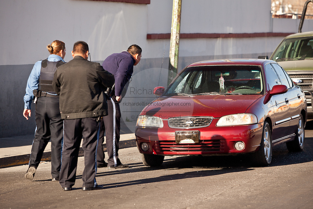 Police investigators peek into a car moments after armed gunman shot dead a former police officer during morning rush hour along a main road in Juarez, Mexico January 16, 2009. The shooting, believed linked to the ongoing drug war which has already claimed more than 40 people since the start of the year. More than 1600 people were killed in Juarez in 2008, making Juarez the most violent city in Mexico.    (Photo by Richard Ellis)