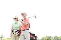 Low angle view of smiling golfers standing against clear sky