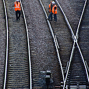 Railroad workers walking on converging railroad tracks