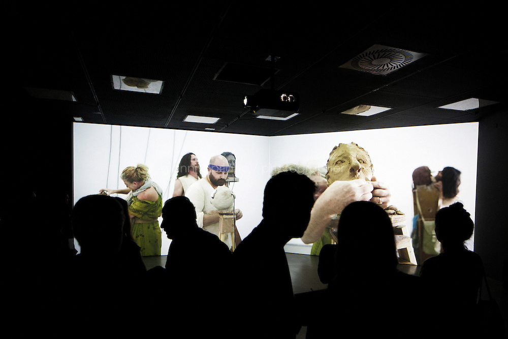 VENICE, ITALY - 29 MAY 2013: Visitors watch the video of Gilad Ratman's instsallation &quot;The Workshop&quot; (2013) at the Israeli Pavillon, Giardini of the Biennale, in Venice, Italy, on May 29th 20113. <br /> <br /> &quot;The Workshop&quot; (2013), a multi-channel site-specific installation, is based on a fictional journey from Israel to Venice taken by a small community of people. Their epic voyage starts in the caves of Israel, weaves through tracherous subterranean passages before bursting through the floor of the Israeli pavillon into a workshop, sculpting themselves in clay they have have transported from Israel. Gilad Ratman's presentation reflects on the Biennale as a utopian model of nations' connectivity. Whilst present-time poltical reality all over the world operates according to the &quot;nation state&quot; concept and a system of globalized capitalism, The Workshop presents a scenario where transit takes place across national borders in hidden underground networks  free. imdetected and unidentified.<br /> <br /> The 55th International Art Exhibition of the Venice Biennale takes place in Venice from June 1st to November 24th, 2013 at the Giardini and at the Arsenale as well as in various venues the city. <br /> <br /> Gianni Cipriano for The New York TImes