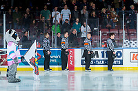 KELOWNA, CANADA - MARCH 10: Ice officials linesman Dave McMahon, referee Adam Byblow, referee Sean Raphael and linesman Kevin Crowell stand on the ice during the national anthem with Rocky Raccoon the mascot of the Kelowna Rockets against the Kamloops Blazers  on March 10, 2018 at Prospera Place in Kelowna, British Columbia, Canada.  (Photo by Marissa Baecker/Shoot the Breeze)  *** Local Caption ***