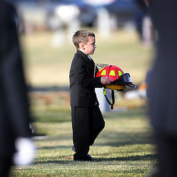 Tuesday November 26, 2013<br /> 5 year old Jack Erickson, son of Eagle Fire Department Captain Brandon Erickson carries his fathers helmet to his funeral at Meridian Cemetery. Erickson, age 36, died at home Thursday following back surgery on Wednesday. <br /> AP PHOTO KYLE GREEN / THE IDAHO STATESMAN