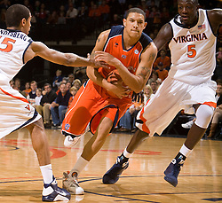 Auburn forward Lucas Hargrove (4) drives past Virginia guard Sylven Landesberg (15) and center Assane Sene (5).  The Auburn Tigers defeated the Virginia Cavaliers 58-56 at the University of Virginia's John Paul Jones Arena  in Charlottesville, VA on December 20, 2008.  (Special to the Daily Progress / Jason O. Watson)