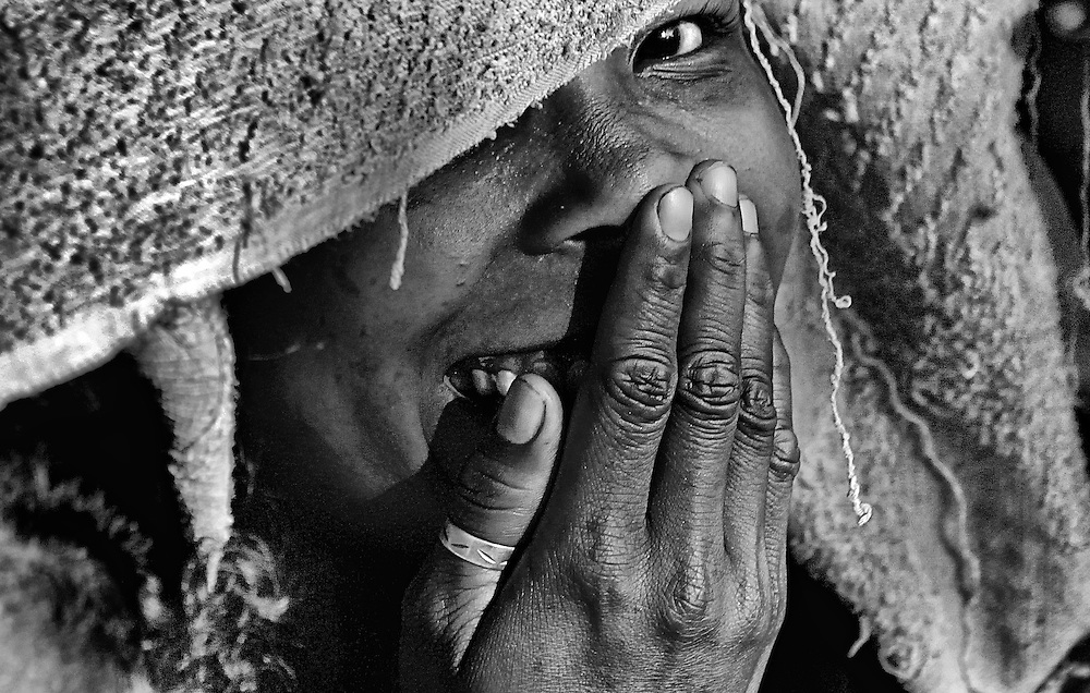 A shy woman peaks from under her towel head cover during a village ceremony on Lembata Island, Indonesia.