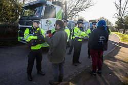 Denham, UK. 6 February, 2020. Police officers move on environmental activists from Save the Colne Valley, Stop HS2 and Extinction Rebellion who were walking at a snail's pace along a road in order to block a security vehicle and truck delivering fencing and other supplies to be used for works associated with the HS2 high-speed rail link close to the river Colne at Denham Ford. Works planned in the immediate vicinity include the felling of trees and the construction of a Bailey bridge, compounds and fencing, some of which in a wetland nature reserve forming part of a Site of Metropolitan Importance for Nature Conservation (SMI).