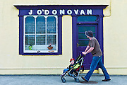 Man wheels child in stroller past J'ODonovan shop front at Courtmacsherry, County Cork, Ireland