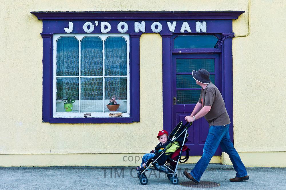 Man wheels child in stroller past J'ODonovan shop front at Courtmacsherry, County Cork, Ireland