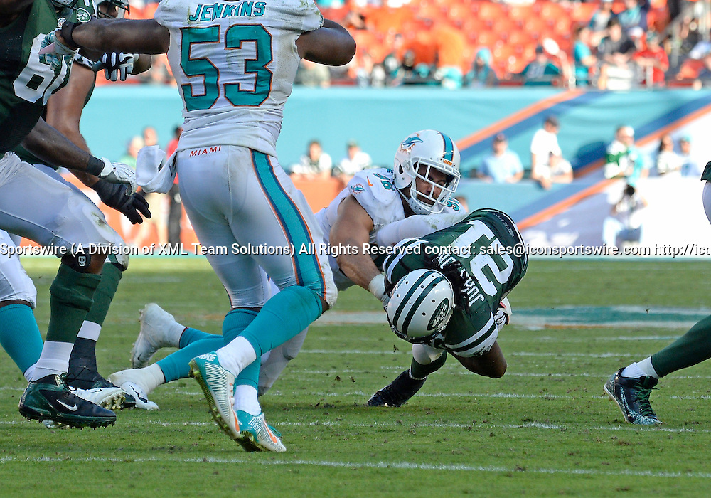 28 December 2014: Miami Dolphins Defensive Tackle Jared Odrick (98) [9012] tackles New York Jets Running Back Chris Johnson (21) [10284] in the Jet's 37-24 victory at Sun Life Stadium, Miami, Florida.